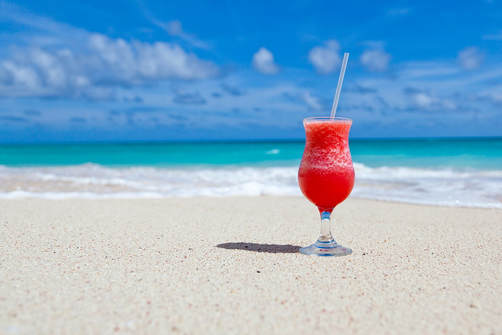 picture of a tropical drink on a white sandy beach
