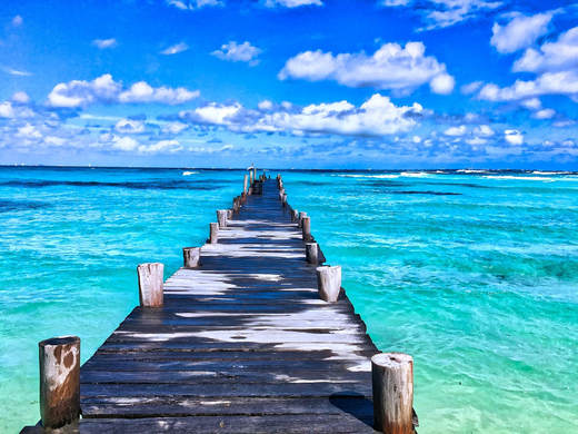picture of a long dock extending into a blue green ocean
