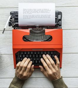 photo of a typewriter with two hands typing